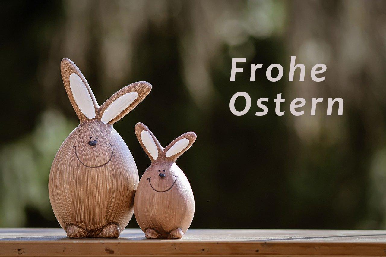 """zwei Osterhasen aus Holz mit der Beschriftung """"Frohe Ostern"""""""